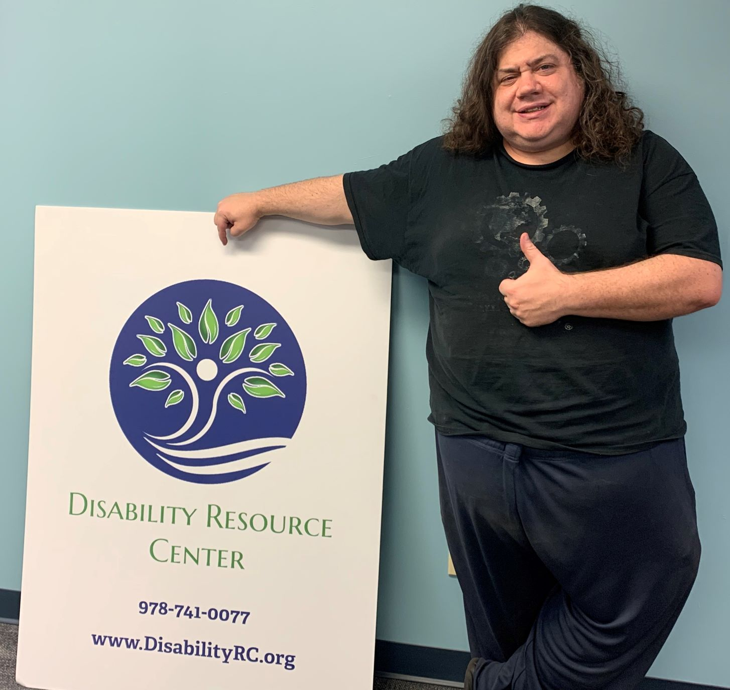 A white man with long curly brown hair leaning on a Disability Resource Center poster giving a thumbs up and a smile