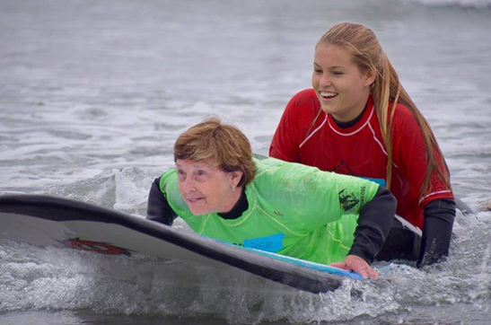 Image of a woman with a green shirt getting help from another woman with a red shirt to surf in the water
